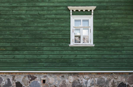 Window with white decorative frame in an old green wooden wall, architectural background texture 版權商用圖片