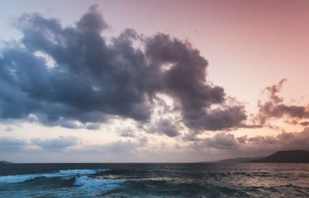 Stormy Sea is under dramatic cloudy sky on a sunset. Propriano, Corsica island, France