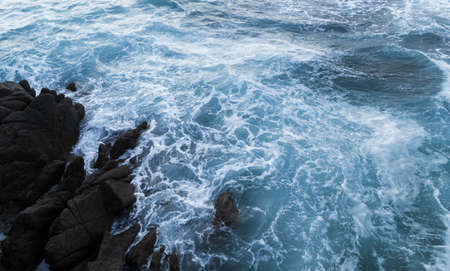 Stormy waves and rocks in sea water. Propriano, Corsica island, France