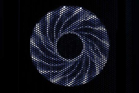Illuminated PC cooler fan in dark case, front view 版權商用圖片