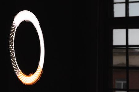Circular LED light glowing in dark photo studio