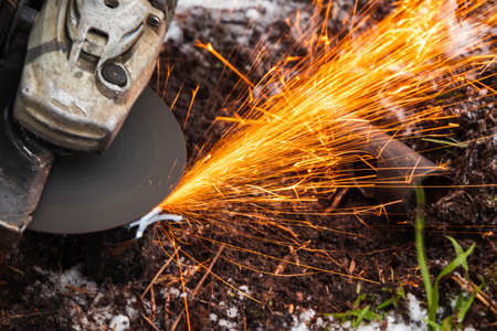 Angle grinder machine works with bright sparks stream, close up photo