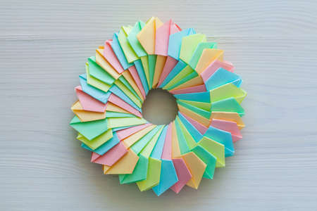 Origami, abstract parametric ring structure made of colorful paper sheets lay on a white desk, top view