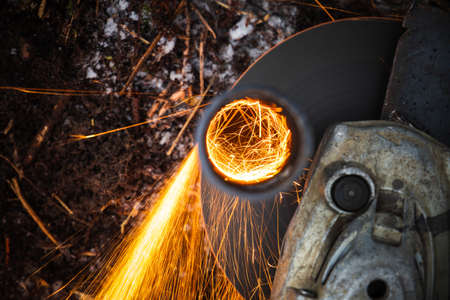 Angle grinder machine cutting metal tube with bright sparks stream, top view, close up photo with selective focus 版權商用圖片