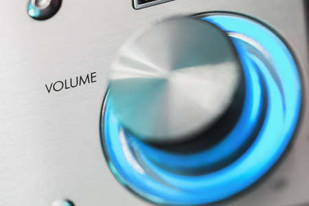 Shiny metallic volume control knob with blue LED illumination, close up photo with selective soft focus on Volume text