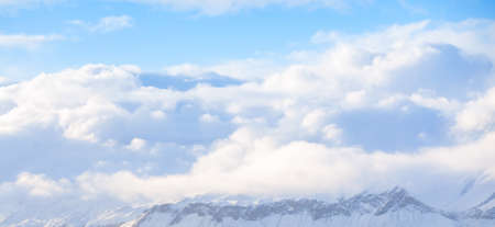 Panoramic mountain landscape with snowy peaks under white cumulus clouds on a daytime. Natural background photo
