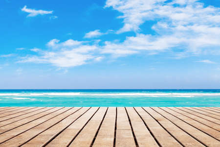 Wooden pier perspective view with bright ocean seascape on a background