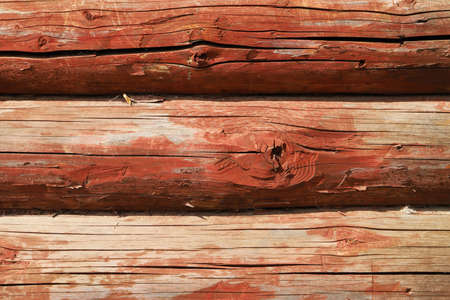Old red wooden wall made of logs, background photo texture