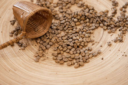 Dry green coffee beans and wicker cup lay on a wooden table