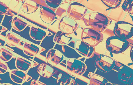 Assortment of sunglasses is on a counter. Close-up photo with selective soft focus and vintage tonal correction filter effect