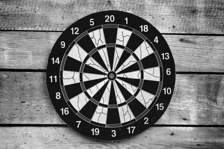 Dartboard mounted on a wooden wall, front view. Black and white photo background