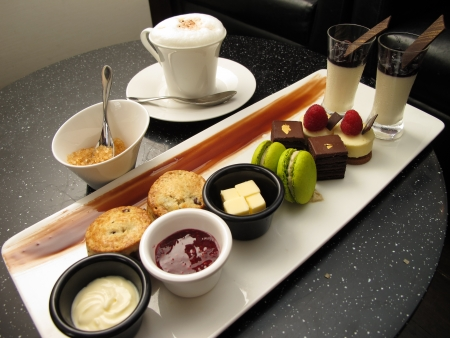 A afternoon tea set consisting of a collection of pastries and a cup of cappuccino. photo