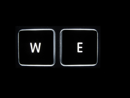 backlit keyboard: Backlit keyboard buttons showing WE isolated on a black background Stock Photo