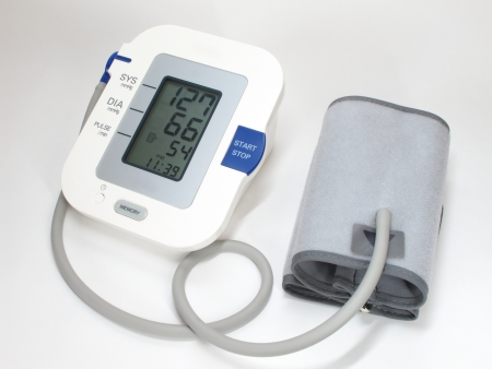 A modern blood pressure monitor and cuff. On white. photo