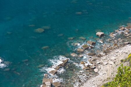 define: Rocky beach and clear waters that define the Cinque Terre region Stock Photo