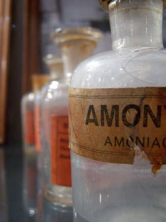 tagged: Some bottles of old medicines on a shelf. The first is tagged ammonia. They were part of the tools used in old Orient Express train, now on show in Istanbul railway station. The bottles have bubbles and a grainy look that give them character Stock Photo
