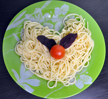 boiled spaghetti on a green plate with tomatoes and basil