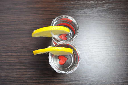 two glasses of tequila with a heart on the bottom and slices of lemon
