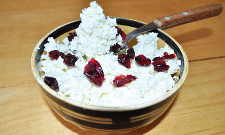 white granular curd in a bowl with cranberries and a spoon