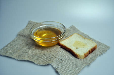 a container with honey on burlap with bread and a spoon for honey