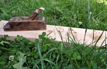 planed board with sawdust and a plane on a background of green grass