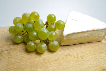 cheese and fruits - a white piece of cheese with a sprig of green grapes