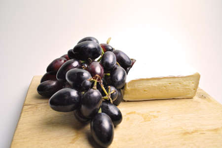 cheese and fruit - a white piece of cheese with a branch of blue grapes