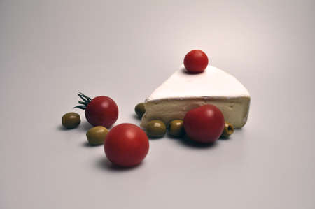 cheese and vegetables - a white piece of cheese with bright red tomatoes