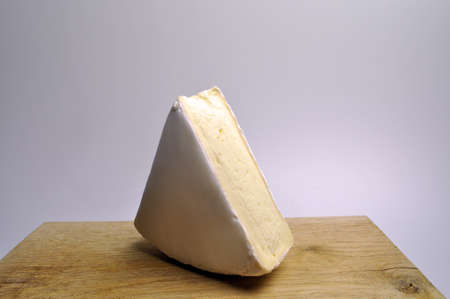 white piece of cheese on a brown wooden board Banco de Imagens