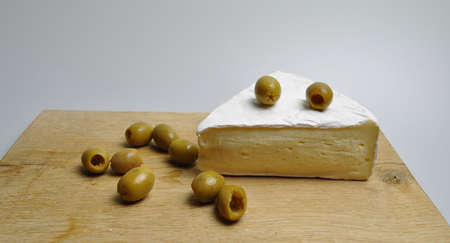 cheese and vegetables - a white piece of cheese with green olives