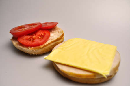 fast food - burger with sausage, cheese and tomato, ingredients for a burger