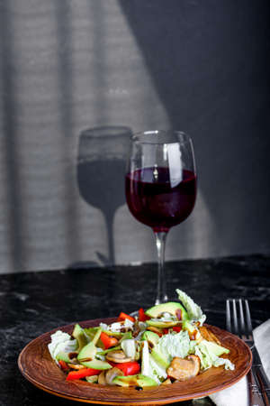 Appetizing salad of fresh vegetables and a glass of wine on the table