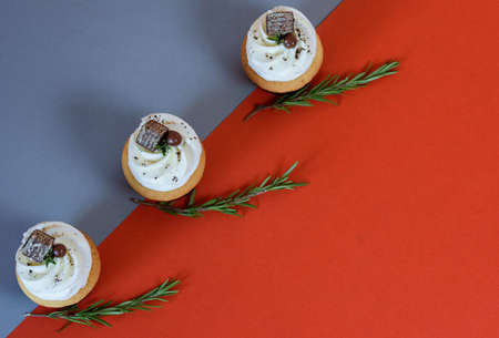 Delicious cupcakes with sprigs of rasmarin on a colored background