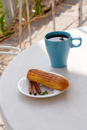 Aromatic coffee in a blue cup with eclairs in a summer cafe. Spring, cinnamon, leaf sprigs.