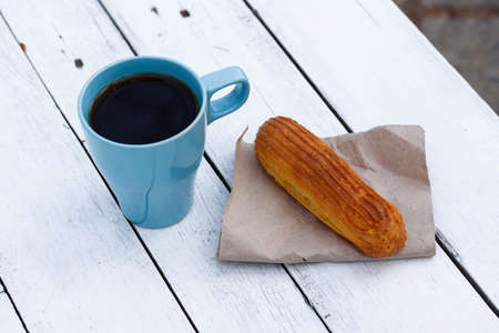 Aromatic coffee in a blue cup with eclairs in a summer cafe.