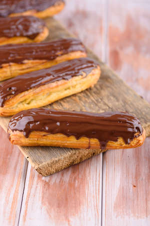 Tasty and beautiful eclairs with chocolate on a wooden board. Appetizing dessert. Party supplies. Flat lay Stockfoto