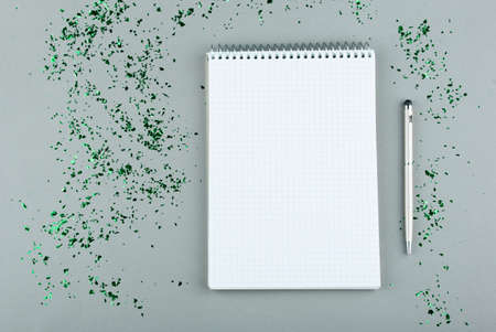 Notepad with white sheets, pen, green glitters on a gray background