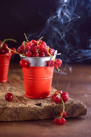 Chilled red currants on a wooden background in a small red bucket