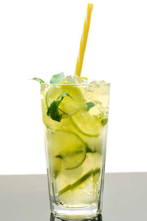 An overhead photo of homemade lemonade in glasses, with fresh lemons, mint, and ice cubes, on a white background with copy space