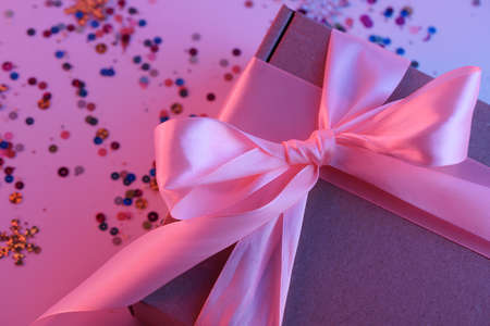Gift box with a pink ribbon in neon light, with a pink and blue tint