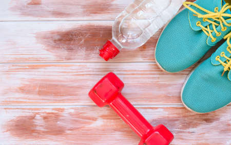 Sports shoes, dumbbells, headphones on the table
