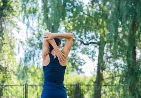 Atletisch meisje dat in een park uitwerkt. Mooie gebosseleerde achterkant. Gezondheid en sport