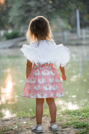 Little girl by the lake with swans, and angel wings. Summer day at sunset.