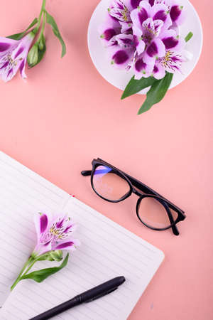View from above. Fragrant tea in a white cup, beautiful flowers, a pink background, a notebook with a pen and glasses. Office. 免版税图像