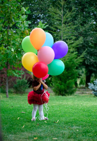Little girl in a beautiful park with gel ballons and a little house. Summer