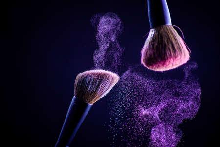 Make-up borstel met roze op de zwarte achtergrond. Gezicht Stockfoto