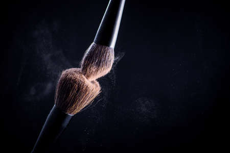Makeup brush with pink on the black background. Face