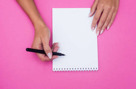 Notebook with pen holds female hands on a pink background. Flat lay