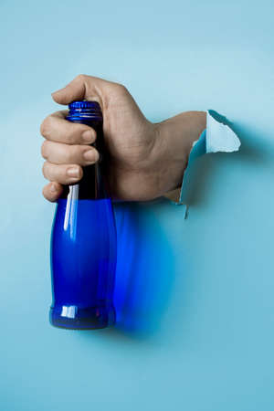 A hand holds a blue water bottle from a torn paper hole. Trend torn paper. Stock Photo