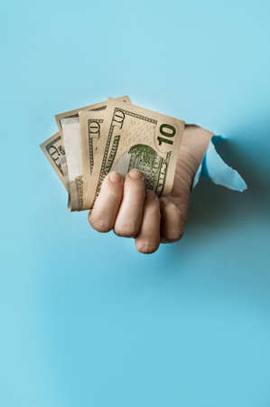 A hand holds a money on the blue torn paper hole. Trend torn paper.
